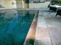 Schwimmbad mit massiver Überlaufrinne und Polygonalplatten.